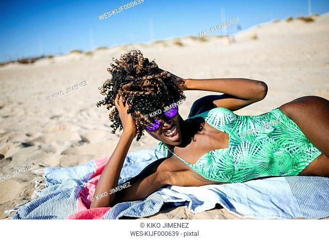 Young woman lying on a towel on the beach