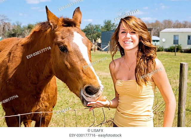 Beautiful teen girl on the farm with her horse