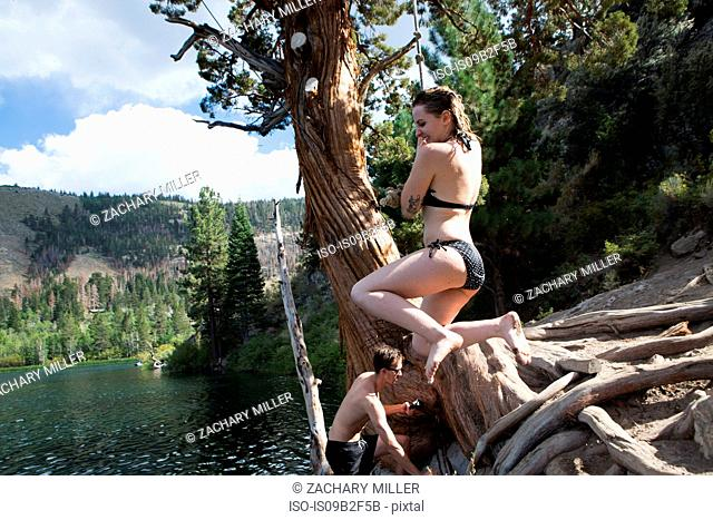 Young woman swinging on rope swing over lake, Mammoth Lakes, California, USA
