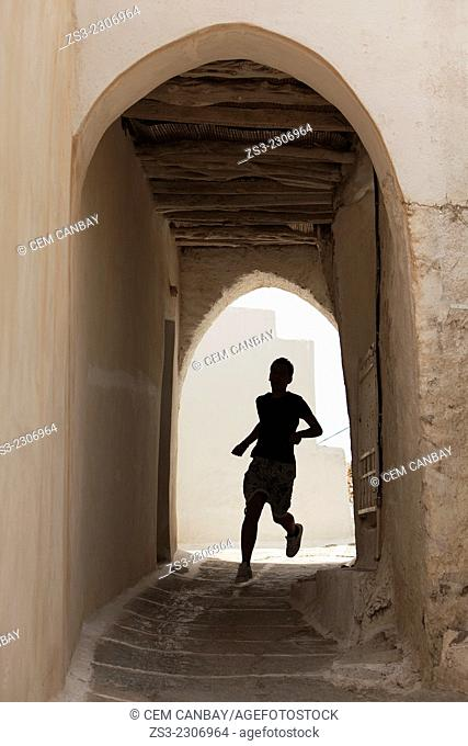 Silhouette of a young man running through an archway at the old town Chora, Ios, Cyclades Islands, Greek Islands, Greece, Europe