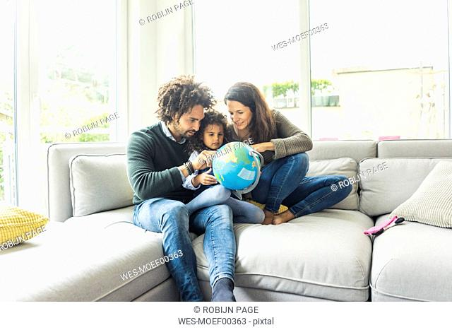 Happy family sitting on couch with globe, daughter learning geography