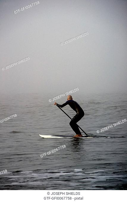 Paddleboarder in the fog