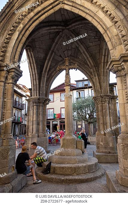 Guimaraes, Portugal - August 9, 2015: People sitting at Salado Monument, built to commemorate the victory of the Salado battle, in Oliveira Square, Guimaraes