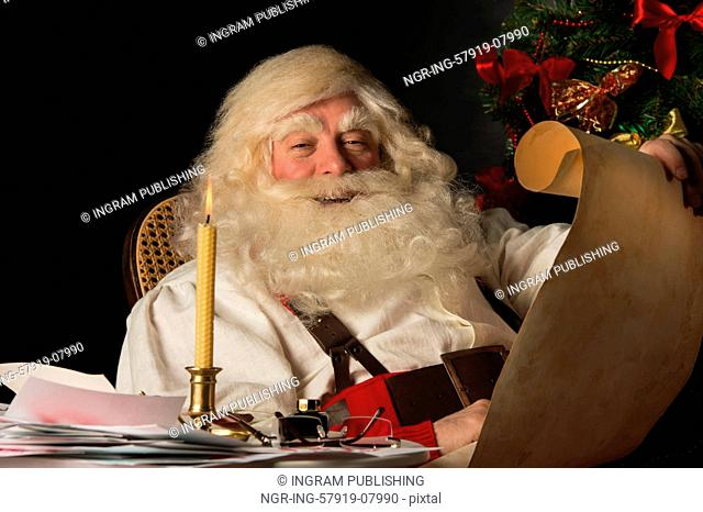 Santa Claus sitting at home and reading old paper roll to do list at night with candle light. Authentic vintage style portrait