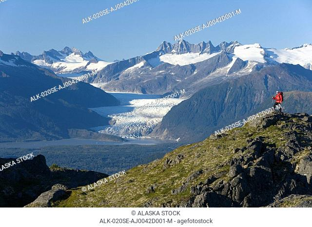 Man hiking in Alaska's Tongass National Forest with view of Mendenhall Glacier near Juneau Alaska southeast Autumn