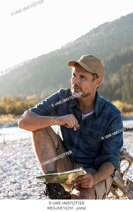 Mature man camping at riverside, sitting on tree trunk with map