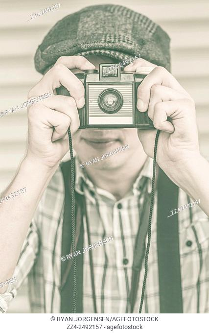 Antique green toned image of a 1950s paparazzi photographer taking a picture with retro film camera. Press