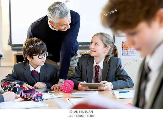 Teacher helping middle school students doing homework in classroom