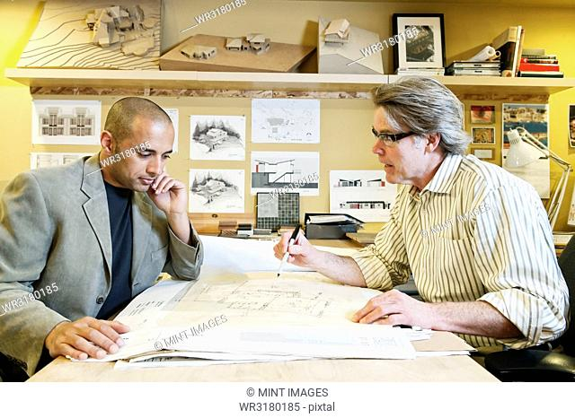 A multi-ethnic team of two male architects working on plans for a new home in an architect's office
