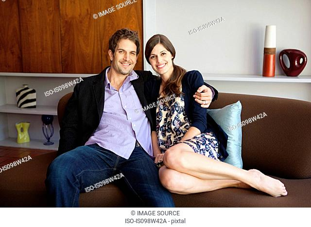 Couple sitting on sofa, portrait