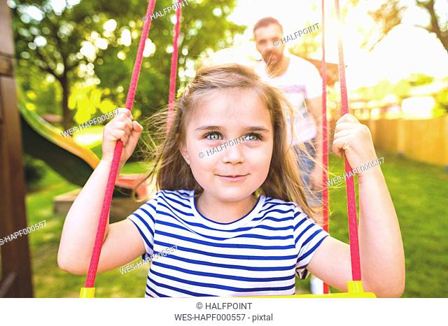 Portrait of happy little girl on a swing with father in the background