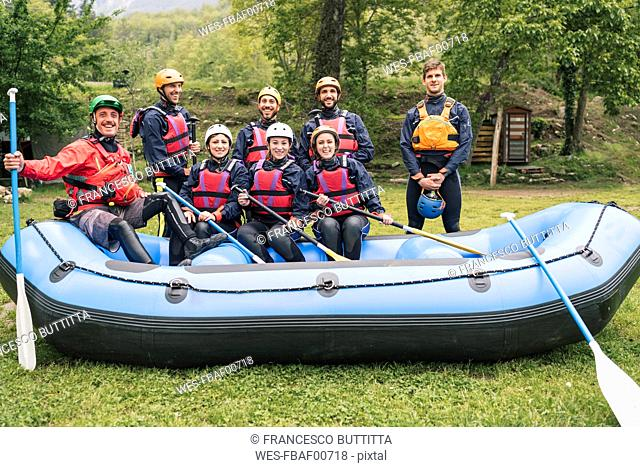 Instructor and group of friends at a rafting class posing in boat