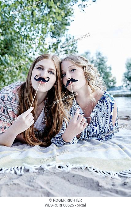 Portrait of two teenage girls with paper moustaches lying on blanket on the beach