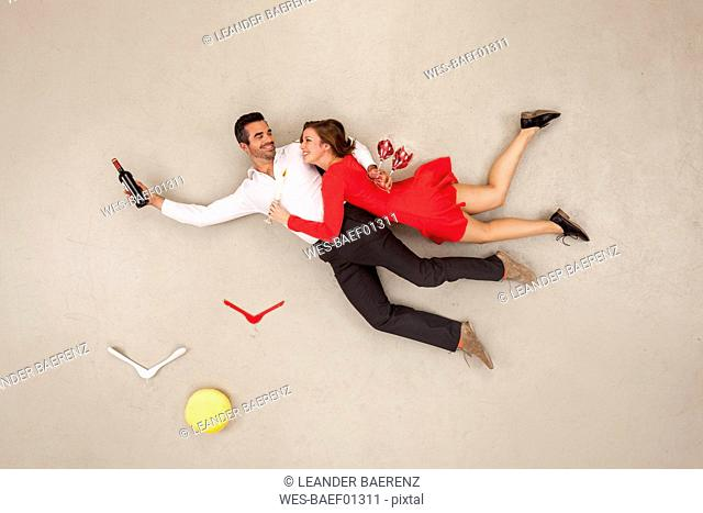 Couple flying with bottle of red wine and glasses