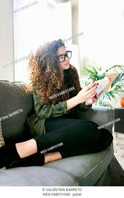 Young woman wearing glasses sitting on couch reading book