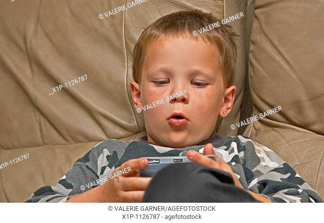 This 5 year old Caucasian boy with freckles is concentrating as he's playing an electronic video game on a beige colored leather couch indoors