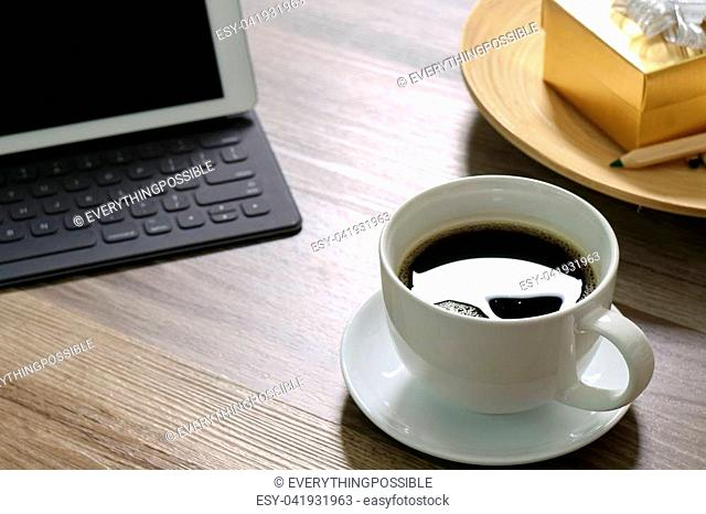 Coffee cup and Digital tablet dock smart keyboard,gold gift box and round wood tray,color pencil on wooden table,filter effect