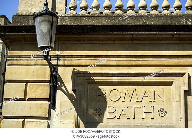 roman bath sign on old bath stone wall Bath England UK