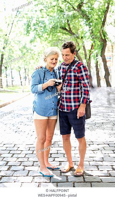 Senior couple wearing shorts and flip-flops looking at camera