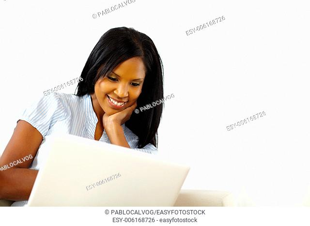 Natural portrait of a calm young woman working on laptop while resting at home