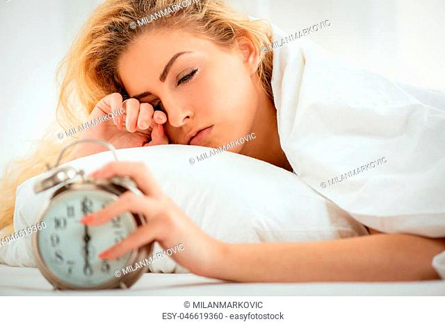 Beautiful young woman sleeping in bed and holding hand on alarm clock. Selective focus. Focus on woman