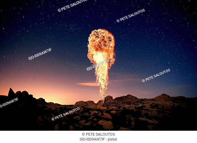 Fire rising up from rocky landscape against starry night sky