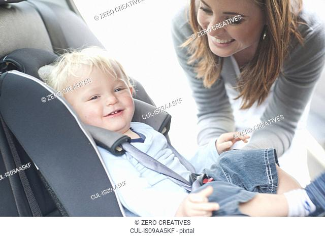 Mother checking baby son in back seat of car