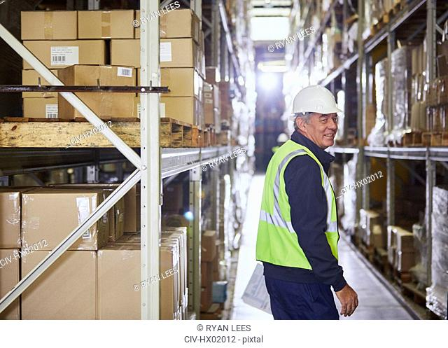 Portrait smiling worker in distribution warehouse aisle