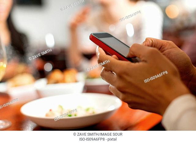 Woman texting during meal with friends