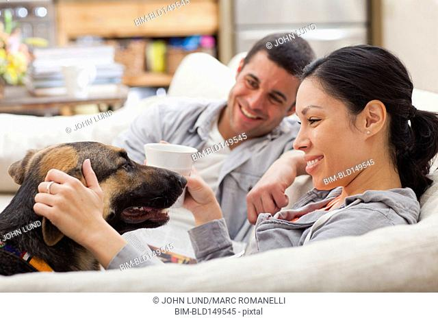 Couple sitting on sofa and petting dog