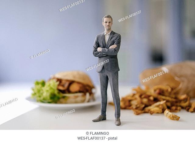 Miniature businessman figurine standing next to fast food