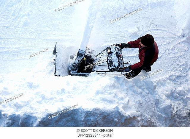 Directly Above A Man Using A Snowblower; Homer, Alaska, United States Of America