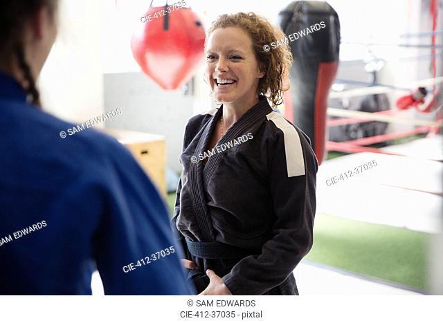 Smiling women practicing judo in gym