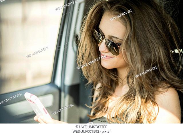 Portrait of smiling teenage girl with sunglasses sitting in a car watching her smartphone