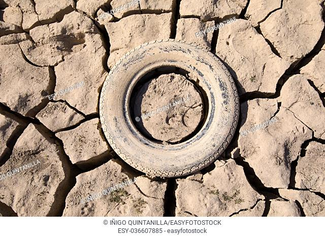 background detail of abandoned tire embedded in dry land, drought in Entrepenas reservoir, in Guadalajara, Castilla, Spain Europe
