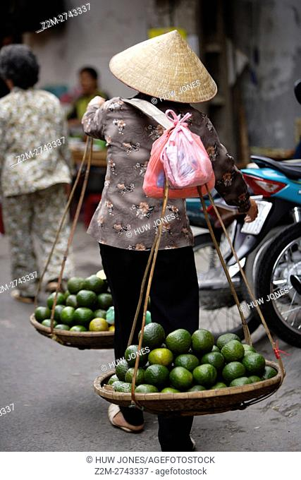 Woman carrying a traditional Vietnamese 'don ganh' yoke, Old Quarter, Hanoi, Vietnam