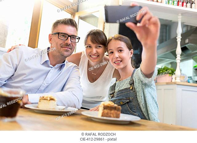 Family with dessert taking selfie at cafe table