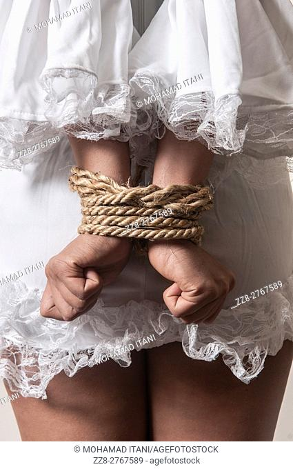 Female hostage hands tired with rope