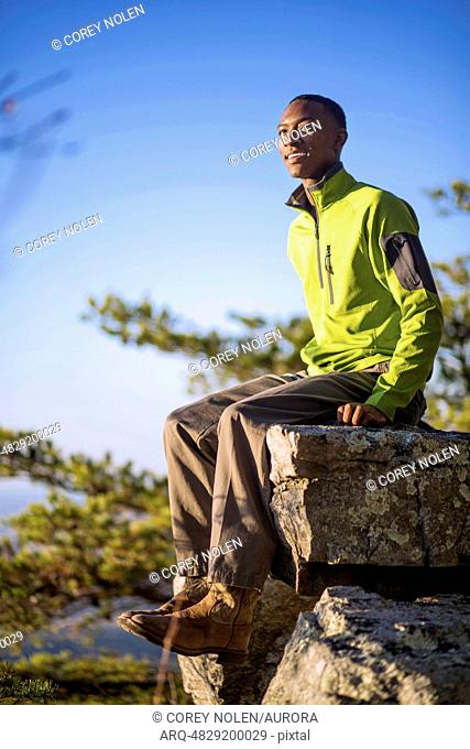 A young man sits on a rock overhang, smiling off camera