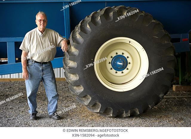 Grain producer standing by tire of a tractor used for harvesting, Montgomery County Maryland USA