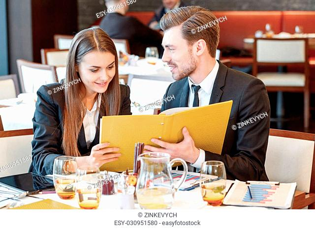 Passionate about business. Young smiling business manager smiles to his female colleague while they look through the business papers during the lunch