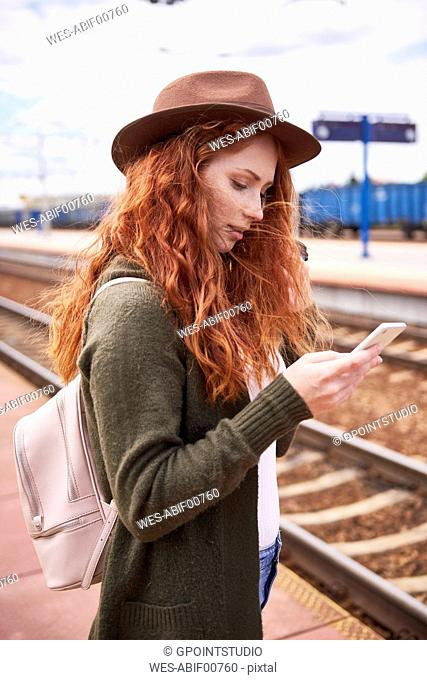 Redheaded woman wearing hat standing at platform looking at cell phone
