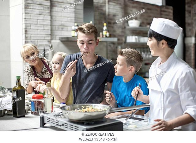 Teenager tasting meal in cooking class