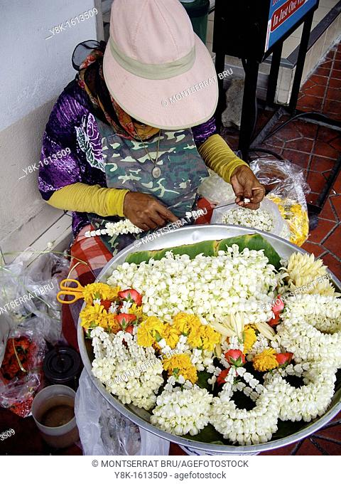 Woman stringing white jasmine flowers in Khao San road, Bangkok, Thailand