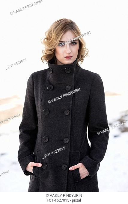 Portrait of confident young woman standing with hands in pockets outdoors