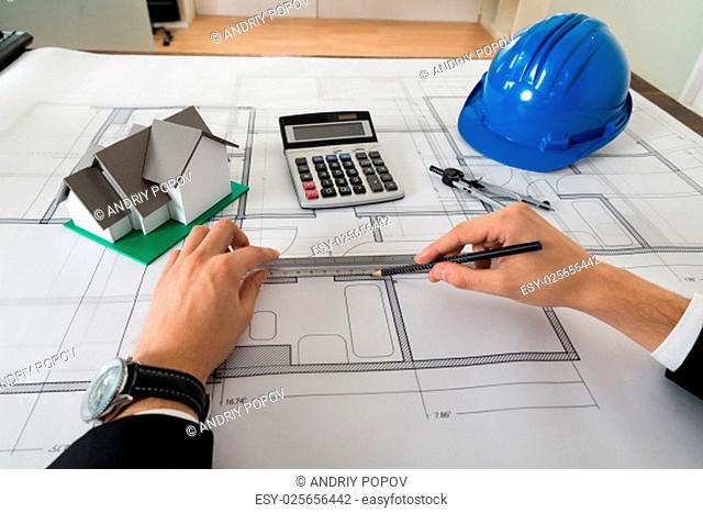 Close-up Of Male Architect Working On Blueprint In Office