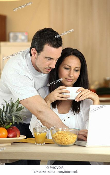 Couple eating breakfast in front of laptop