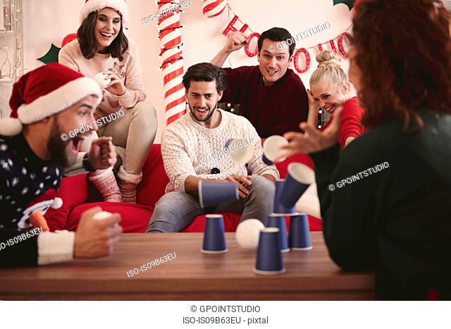 Young adult friends throwing ball at paper cups at christmas party