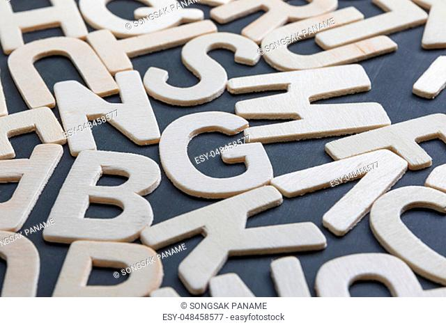 Close up wooden alphabet study english letters, ABC on the blackbroad as a background composition