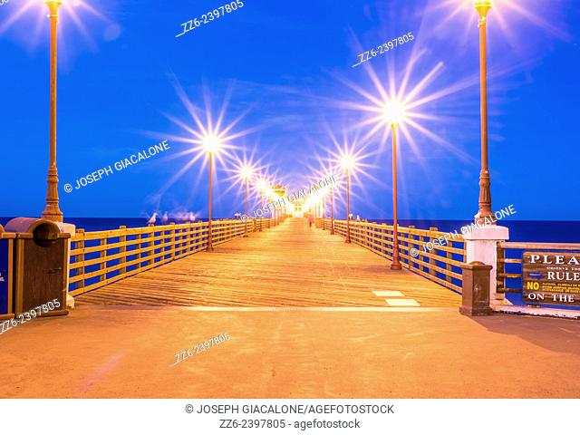 Looking down a row of lamp posts on the Oceanside Pier in the early morning. Oceanside, California, United States